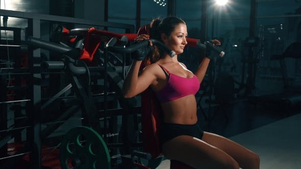 Cover Image for Young Woman Flexing Muscles On Gym Machine