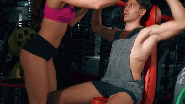 Thumbnail for Young Man And Girl Pumping Muscles On Gym Machine