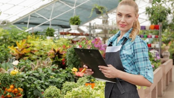Thumbnail for Female Florist Holds Black Tablet At The Garden Centre