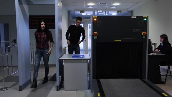 Cover Image for A Man And a Woman Pass Through a Metal Detector At Airport.