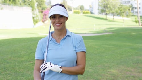 Female Golfer Wearing Visor And Blue Polo Shirt