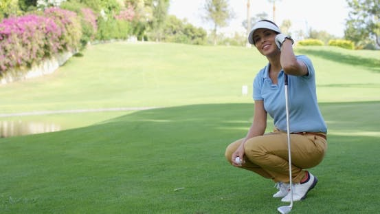 Thumbnail for Smiling Female Golfer With Brown Hair Crouches