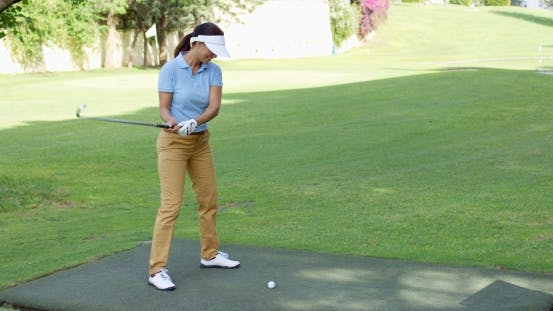 Thumbnail for Young Female Golfer Preparing To Tee Off