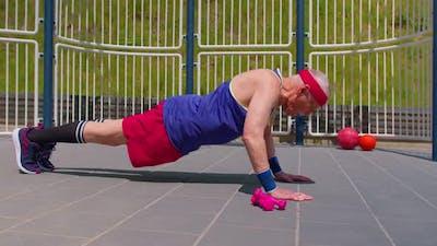 Active Elderly Old Pensioner Man Cardio Morning Aerobics Routine Pushups Exercising on Playground