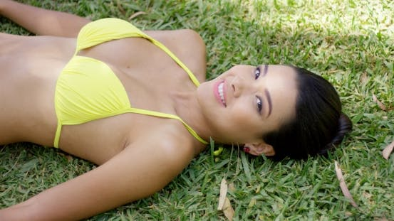 Cover Image for Smiling Young Woman Laying On Grass
