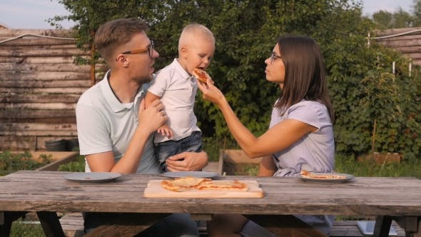 Thumbnail for Young Happy Family Having Picnic In The Garden. Mom, Dad And Son Eating Pizza Outdoors