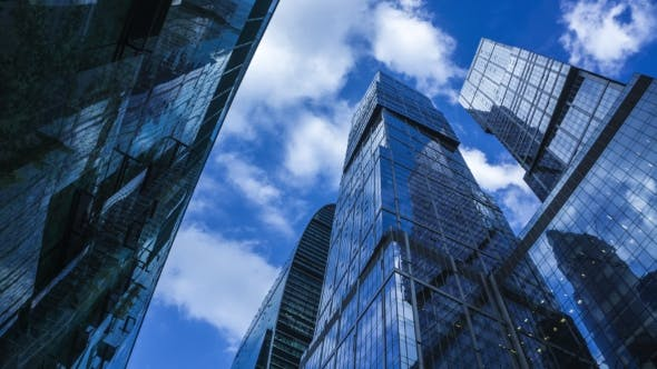 Modern Reflective Skyscrapers Against Cloudy Sky