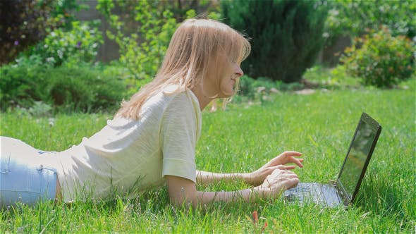 Thumbnail for Beautiful Girl Using Notebook Laying on Grass in Park 1