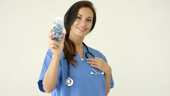 Thumbnail for Young Brown Haired Doctor In Scrubs Holds Bottle