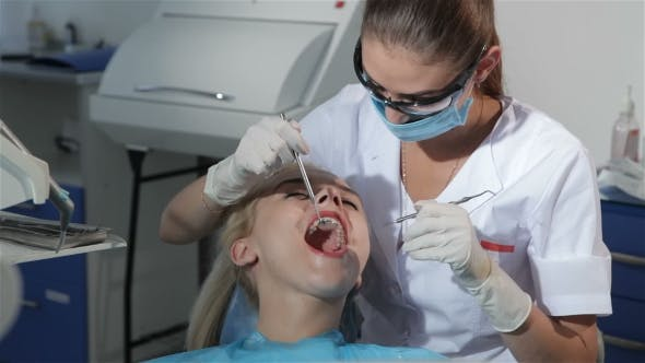 Thumbnail for Dental Surgeon Applies Dental Probe To Examine Patient's Teeth