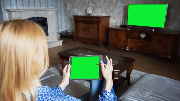 Thumbnail for Beautiful Girl Using Tablet PC with Green Screen Sitting on Sofa at Home 5 In Front Of The TV