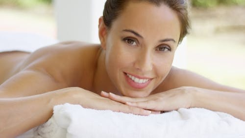 Woman With Chin On Folded Towel Smiles