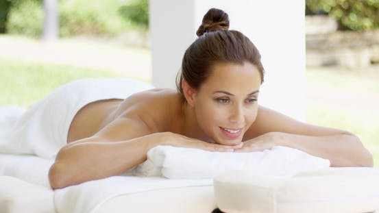 Thumbnail for Naked Woman On Massage Table Smiles As She Rests