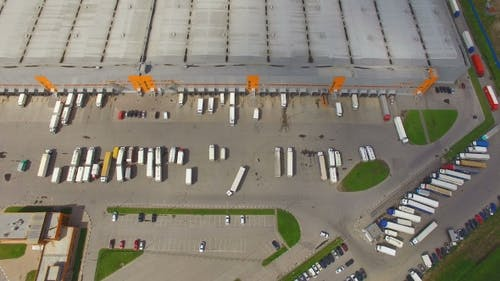 Aerial view of the logistics warehouse with trucks waiting for loading