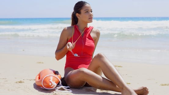 Pretty Lifeguard Sits On Beach And Twirls Whistle