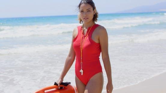 Thumbnail for Beautiful Lifeguard Walking Near Surf On Sunny Day