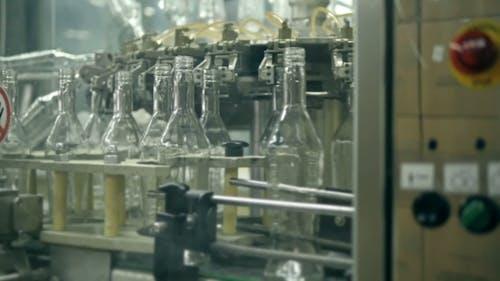 Many Bottles Of Vodka Or Gin On Conveyor Belt In Factory. Bottling Plant