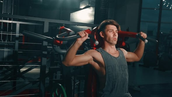 Cover Image for Young Man Flexing Muscles On Gym Machine
