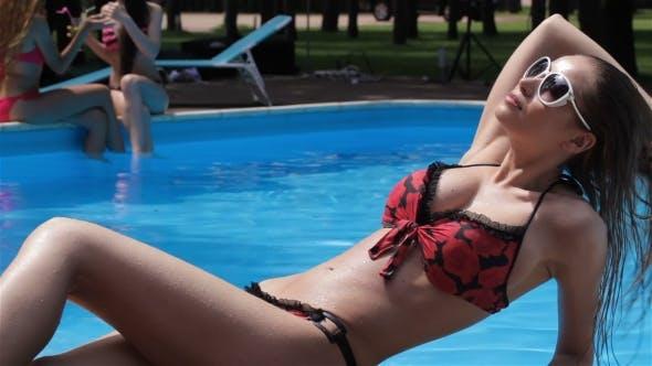 Thumbnail for Frau sitzt auf der schwimmen poolside
