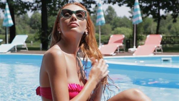 Thumbnail for Frau trocknet Ihr Haar in der Nähe der Schwimmbad