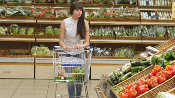 Thumbnail for Young Woman Pushing Cart Along The Grocery Aisles In The Supermarket. Girl Choosing Fresh Vegetables