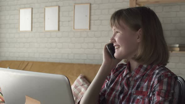 Thumbnail for Teen Girl Communicates With Laptop At Home By Window At Wooden Table