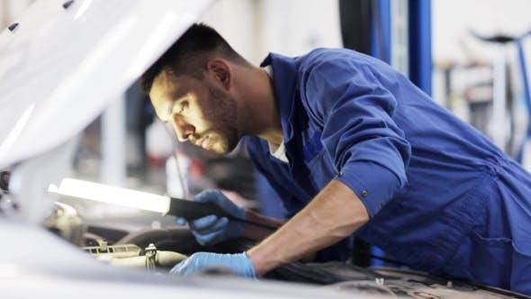 Cover Image for Mechanic Man With Lamp Repairing Car At Workshop 29