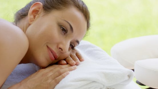 Thumbnail for Woman With Hair Up In a Bun Rests On Folded Towel