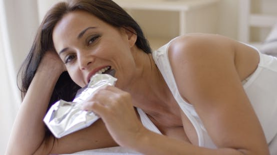 Thumbnail for Adorable Middle Aged Woman Eating Bar Of Dark Chocolate