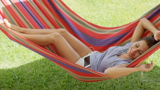 Thumbnail for Happy Young Woman Relaxing In a Colorful Hammock