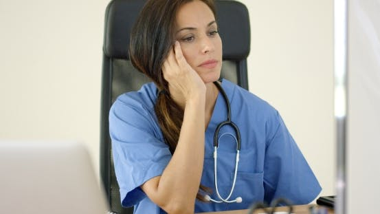 Thumbnail for Serious Female Doctor At Laptop Computer