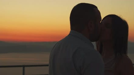 Close up of a young couple kissing at sunset. Spending romantic evening. Arc shot, slow motion.