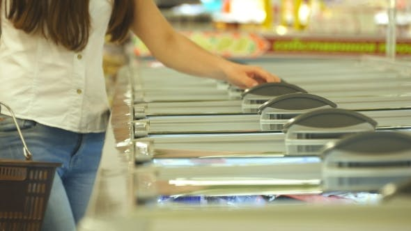 Thumbnail for Young woman taking product from fridge in shop and putting it into the basket