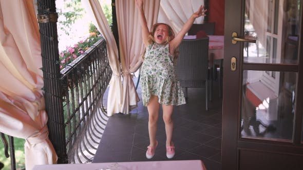 Thumbnail for A Happy Little Girl Is Jumping In The Balcony.