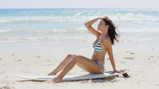 Young Woman Sitting On a Surfboard On The Beach