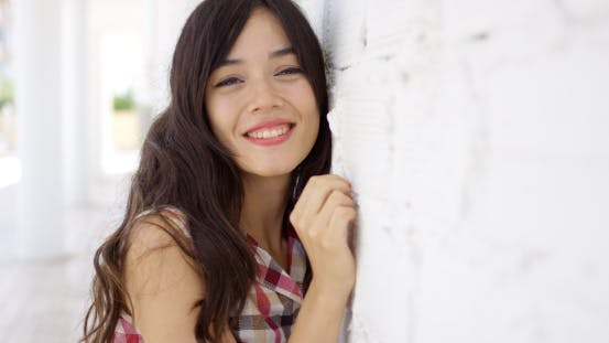 Thumbnail for Happy Young Woman Leaning On a White Wall