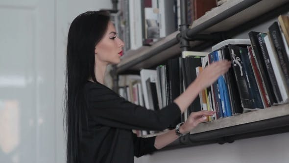 Thumbnail for Woman Takes a Book From The Shelf And Opened.