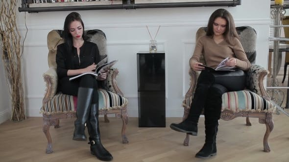 Thumbnail for Two Young Women Sitting Leaf Through Magazines.