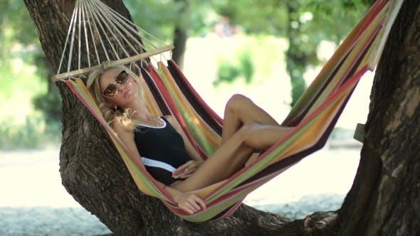 Thumbnail for Woman Lying In Hammock In Tree's Shadow On Beach