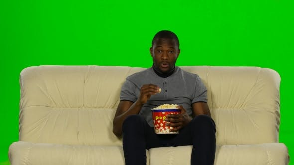 Thumbnail for Man Watching Movie On Couch And Eating Popcorn. Green Screen