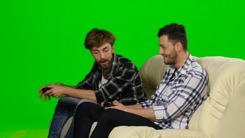 Men Compete In The Game On The Console. Green Screen