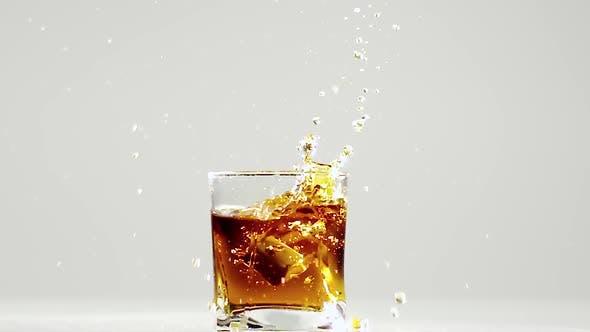 Zwei Eiswürfel fallen in Glas mit Bourbon. Zeitlupe