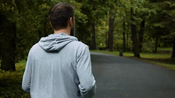 Thumbnail for Young Handsome Runner Outside in Autumn Nature Park with Phone