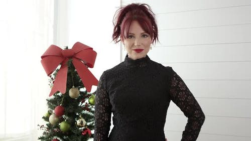 Woman smiling and posing in front of small christmas tree