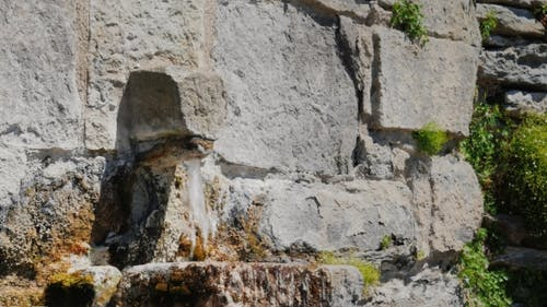 The Water Flows From The Tap In The Old Stone Wall. City Rupit Catalonia