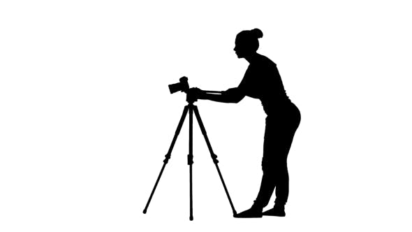 Thumbnail for Operator Works With The Camera On a Tripod. Silhouette.