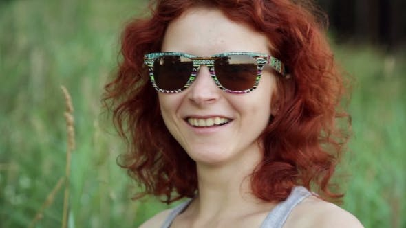 Cover Image for Happy Ginger Woman In Sunglasses Smiling Against Green Grass