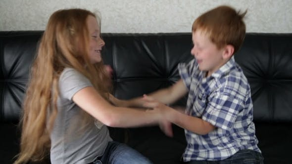 Cover Image for Brother And Sister Fighting And Playing On Sofa