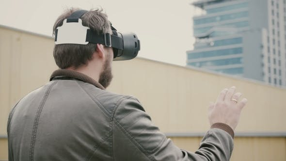 Thumbnail for Bearded Attractive Man Uses Virtual Reality Glasses on the Roof