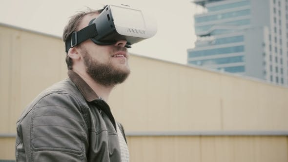 Cover Image for Bearded Attractive Man Uses Virtual Reality Glasses on the Roof